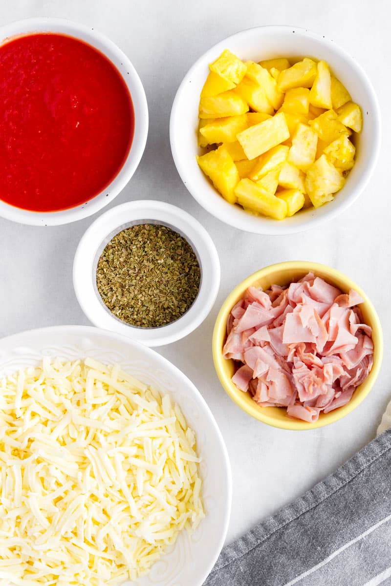 ingredients for hawaiian pizza in arranged in bowls