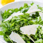 round bowl with arugula salad tossed with lemon dressing and shaved cheese