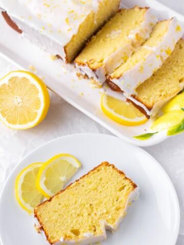 a slice of lemon loaf cake on a plate next to a whole sliced loaf of pound cake