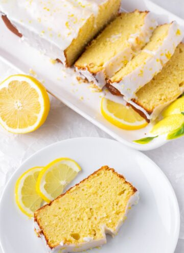 a slice of lemon loaf cake on a plate next to a whole sliced loaf of pound cake