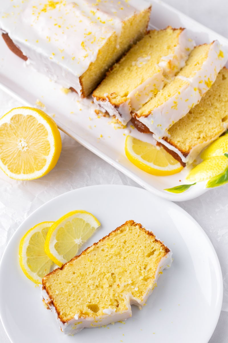 top view of a lemon loaf cake on a plate next to a sliced loaf