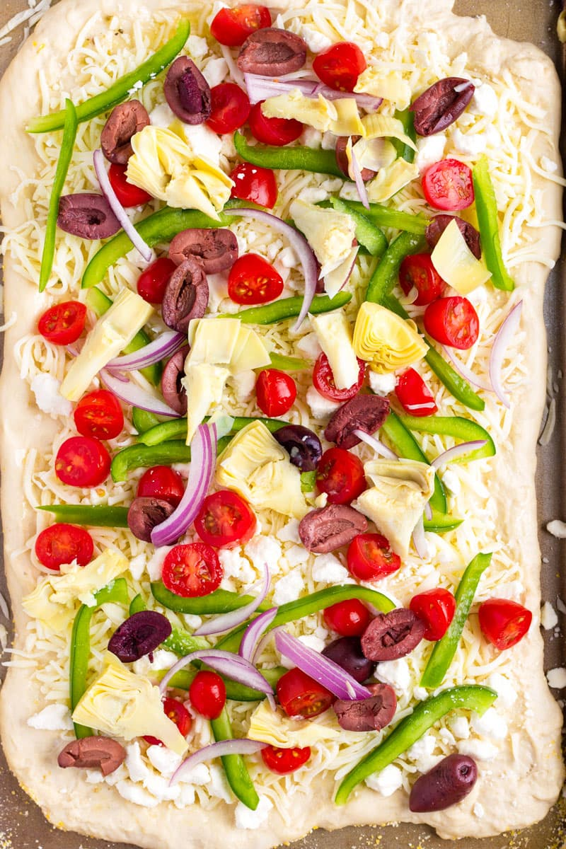 unbaked pizza with cheese, feta, artichokes, tomatoes, green peppers, and olives