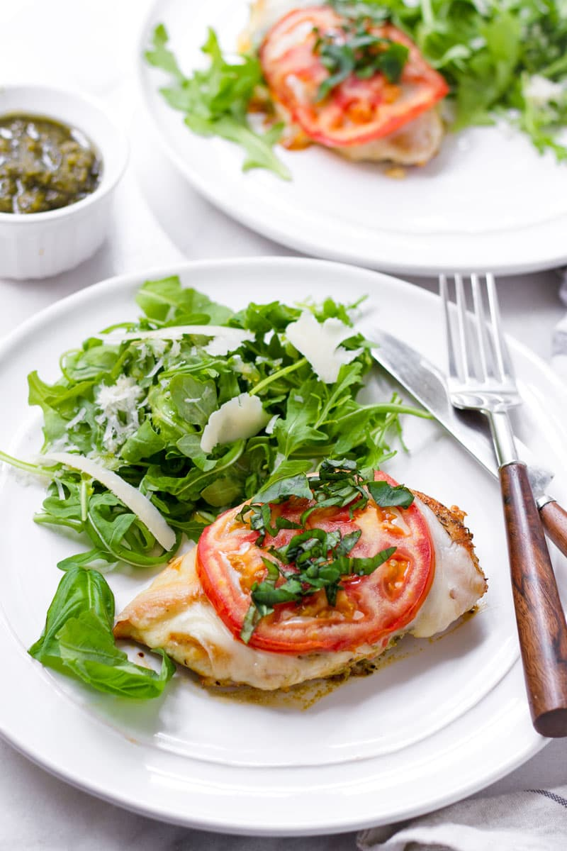 One serving of pan-seared chicken breast topped with pesto, mozzarella, tomato, basil