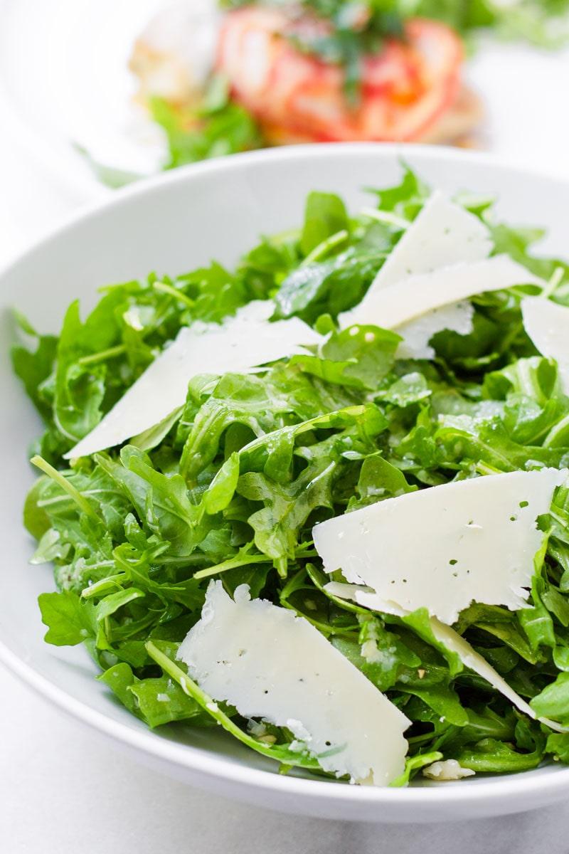 fresh greens salad with baby arugula, lemon dressing, and shaved parmesan cheese