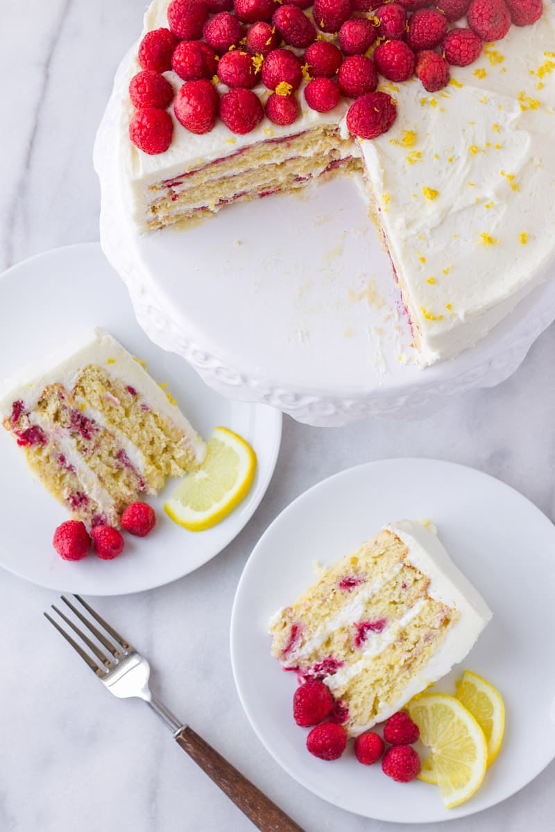 top view of raspberry cake on a cake stand next to two plates with individual cake slices