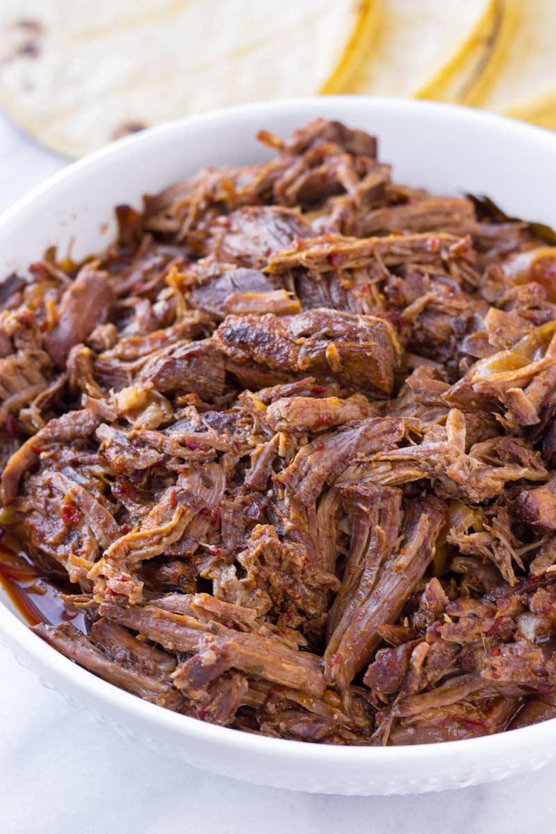 shredded tender meat in a white ceramic bowl