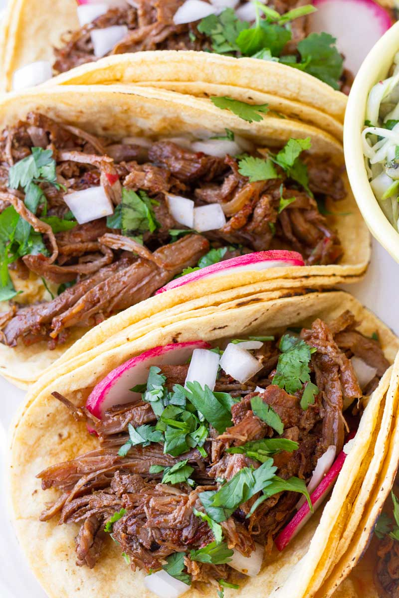 close up of slow cooked barbacoa beef tacos with garnish