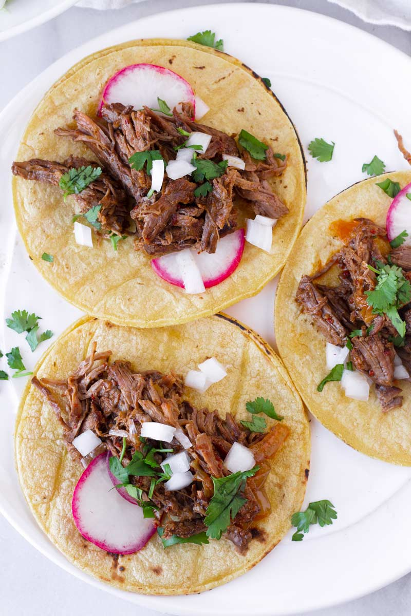 top view of three corn tortillas with barbacoa beef, radishes, cilantro and onions
