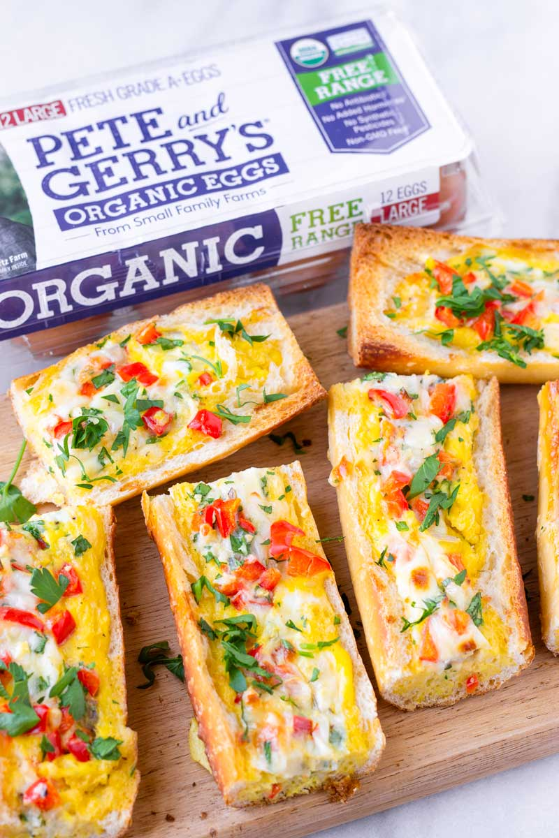 split baguettes baked with egg and veggies on a serving board and case of eggs