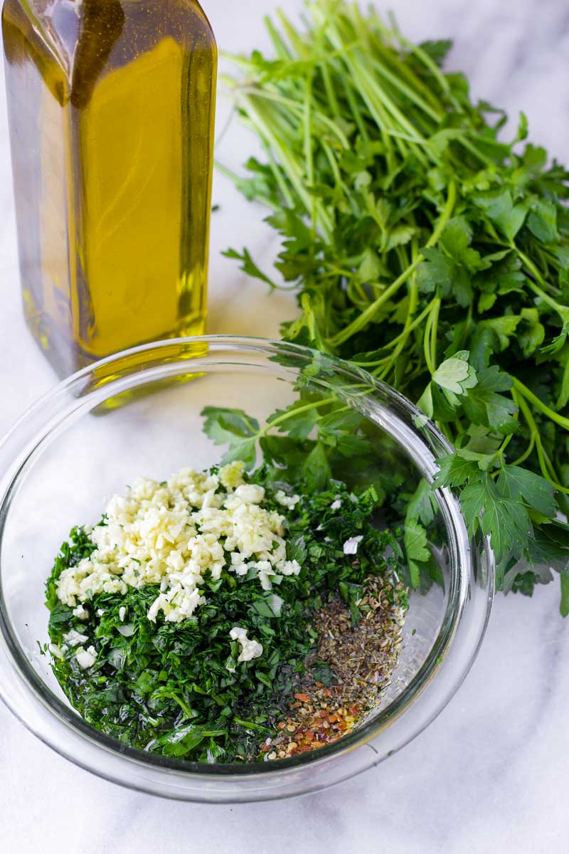 chopped and minced parsley and garlic along with spices, next to olive oil and parsley