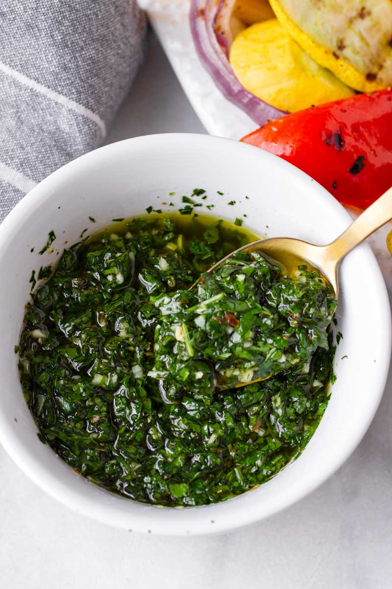 fresh chimichurri being scooped with a golden spoon