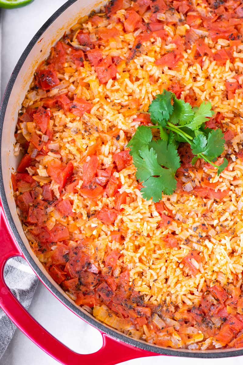 tender rice with cooked diced tomatoes on top and cilantro garnish in a pot