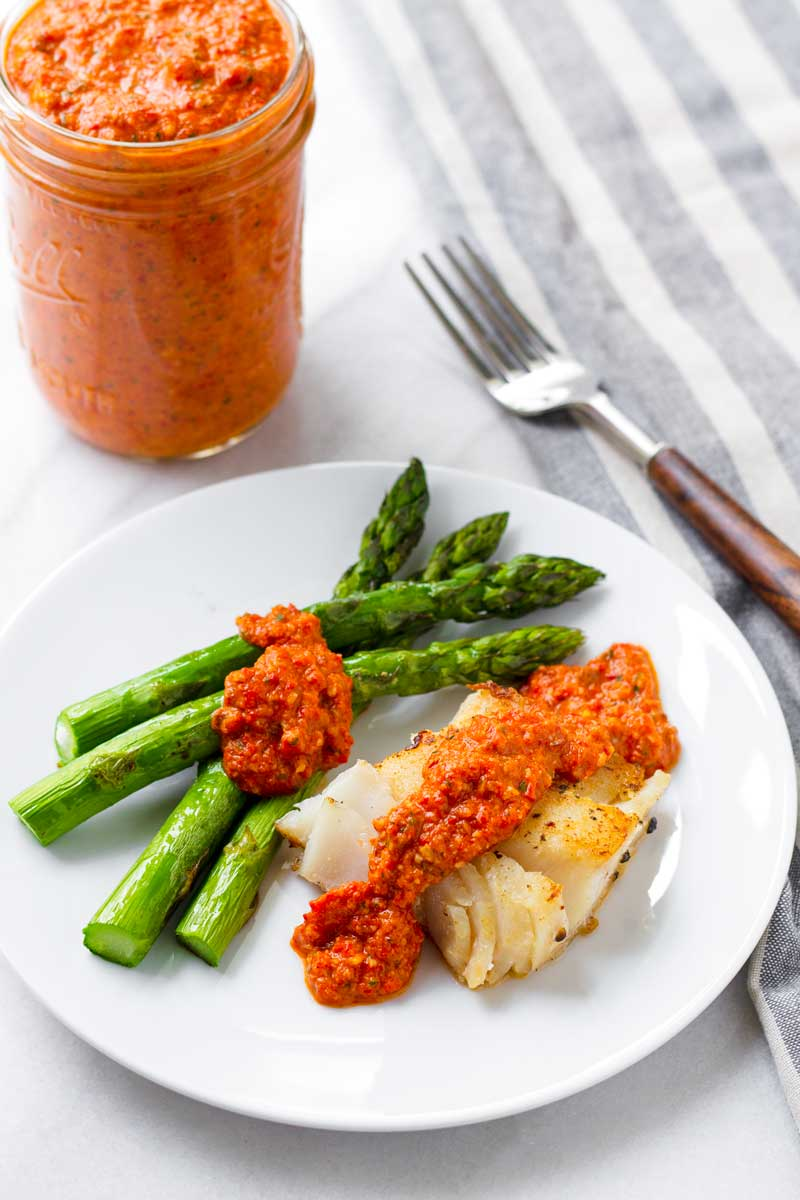 pan fried fish and asparagus on a plate with romesco