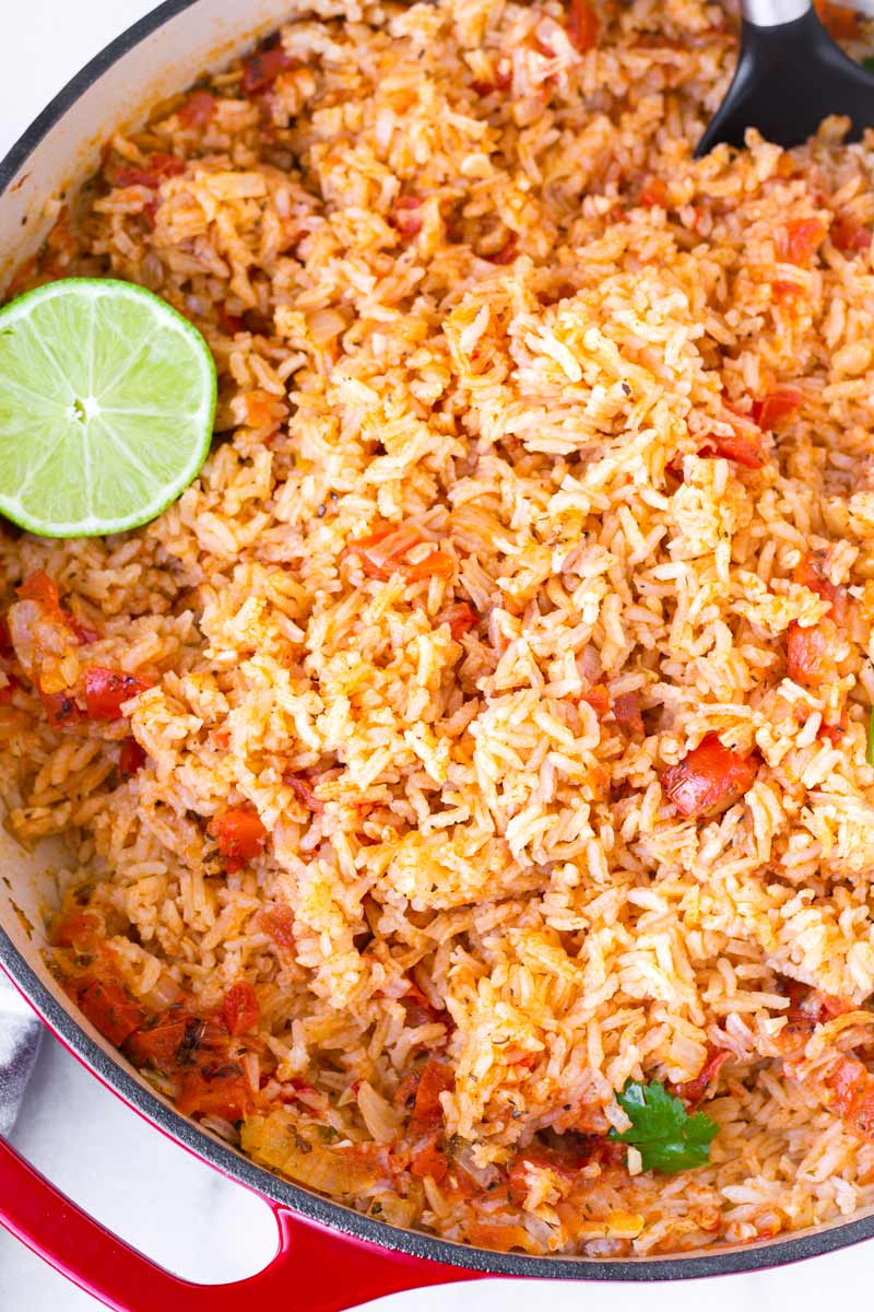 top view of prepared mexican rice with lime garnish in a red pot