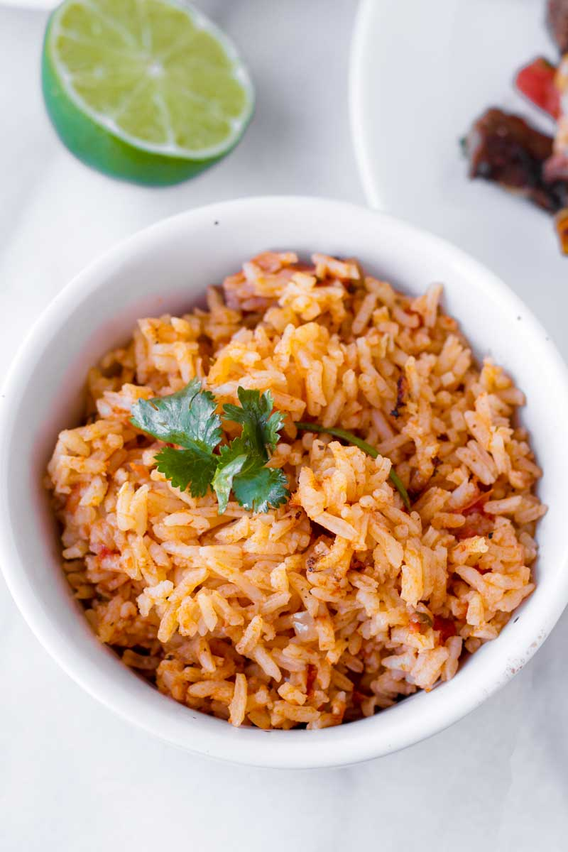 latin inspired rice served in a small bowl with half a lemon in the background