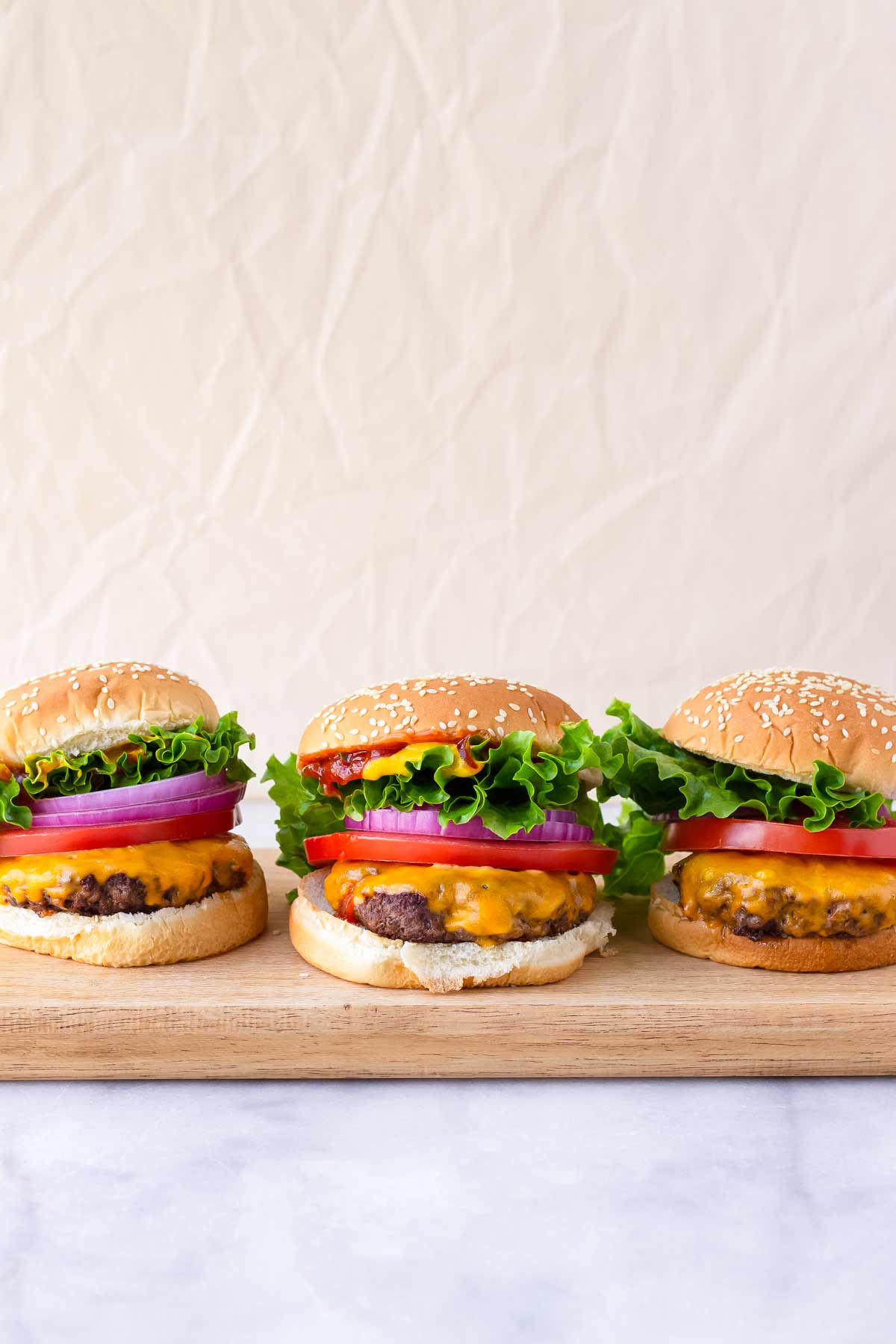 straight view three assembled American burgers arranged on a board