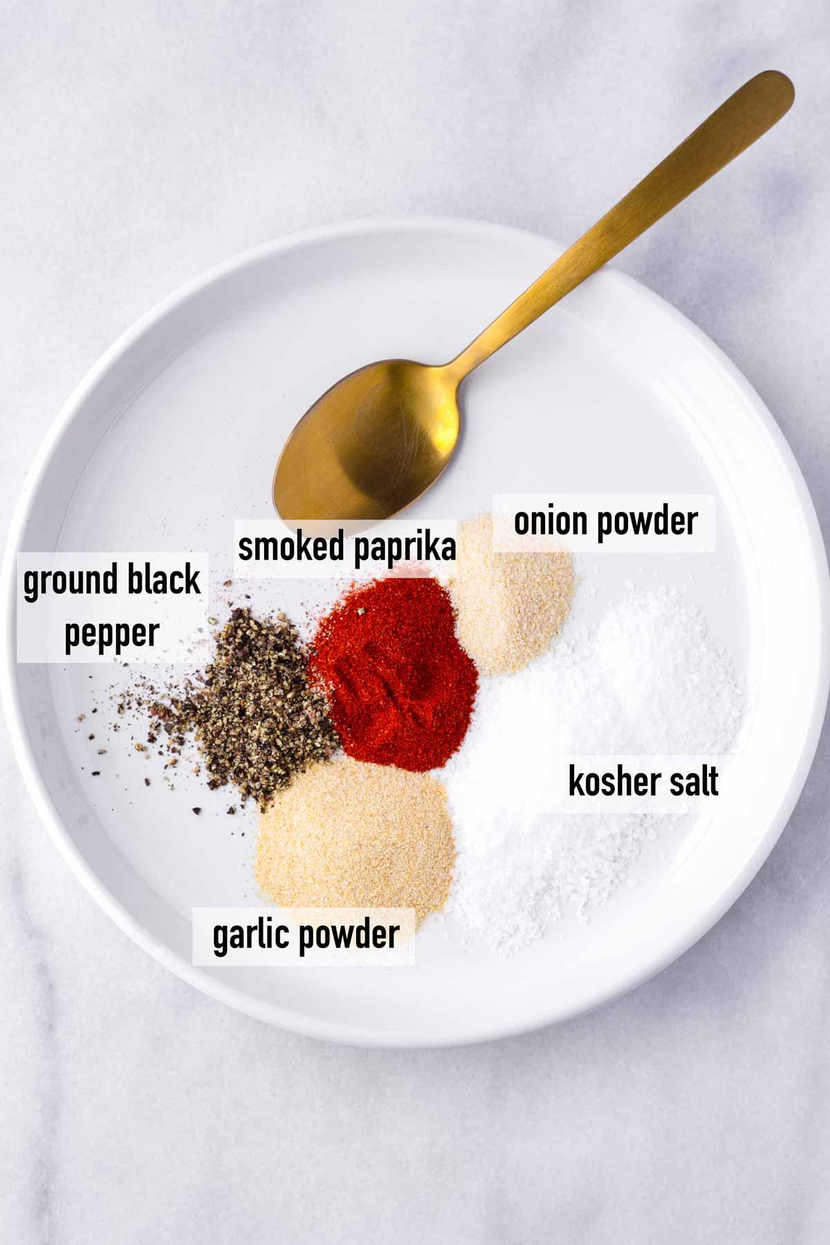 labeled black pepper, paprika, garlic powder, onion powder, salt and pepper arranged on a plate