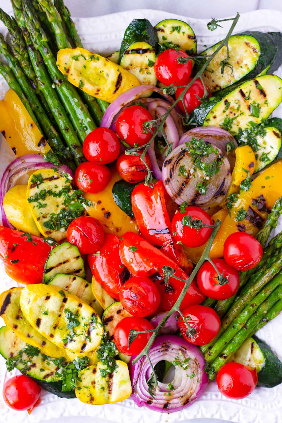 grilled zucchini, asparagus, tomatoes, onions, and peppers on a platter