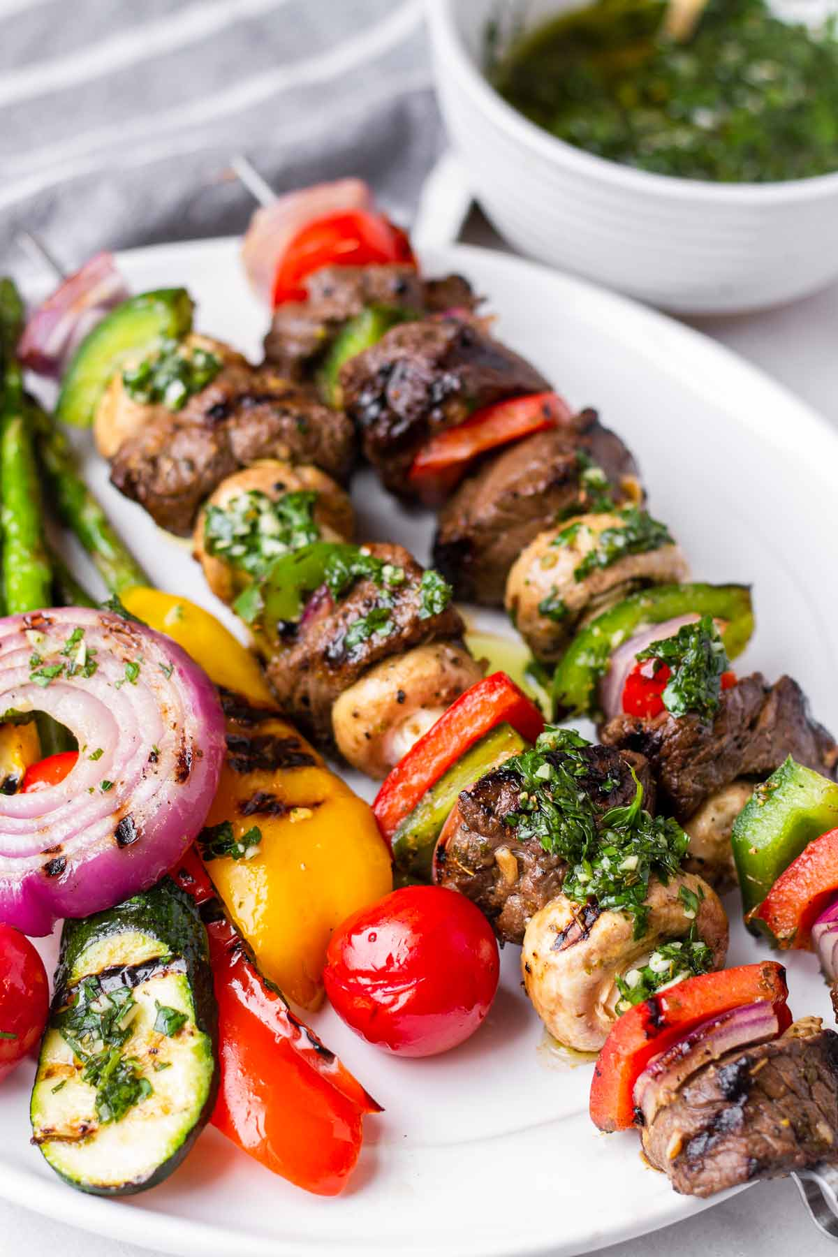 two steak and veggie skewers with grilled vegetables on the side