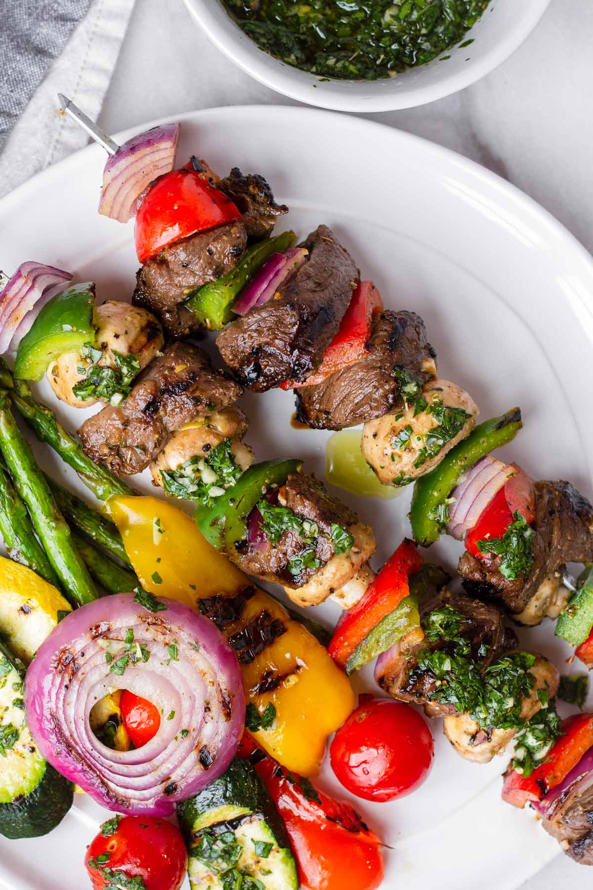 Plate with two meat and vegetable skewers and assorted seasonal veggies
