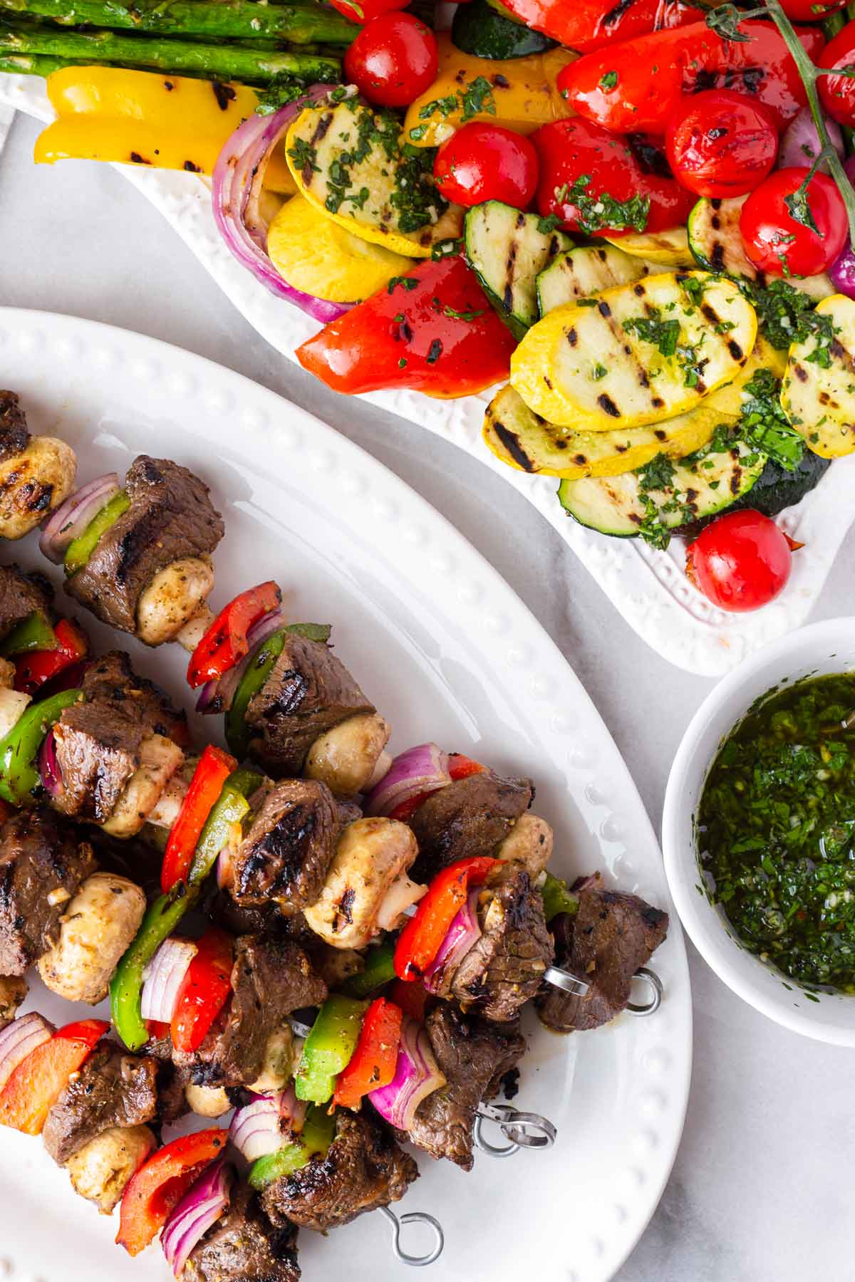 oval plate with grilled steak kabobs and a grilled vegetable platter with a side of chimichurri