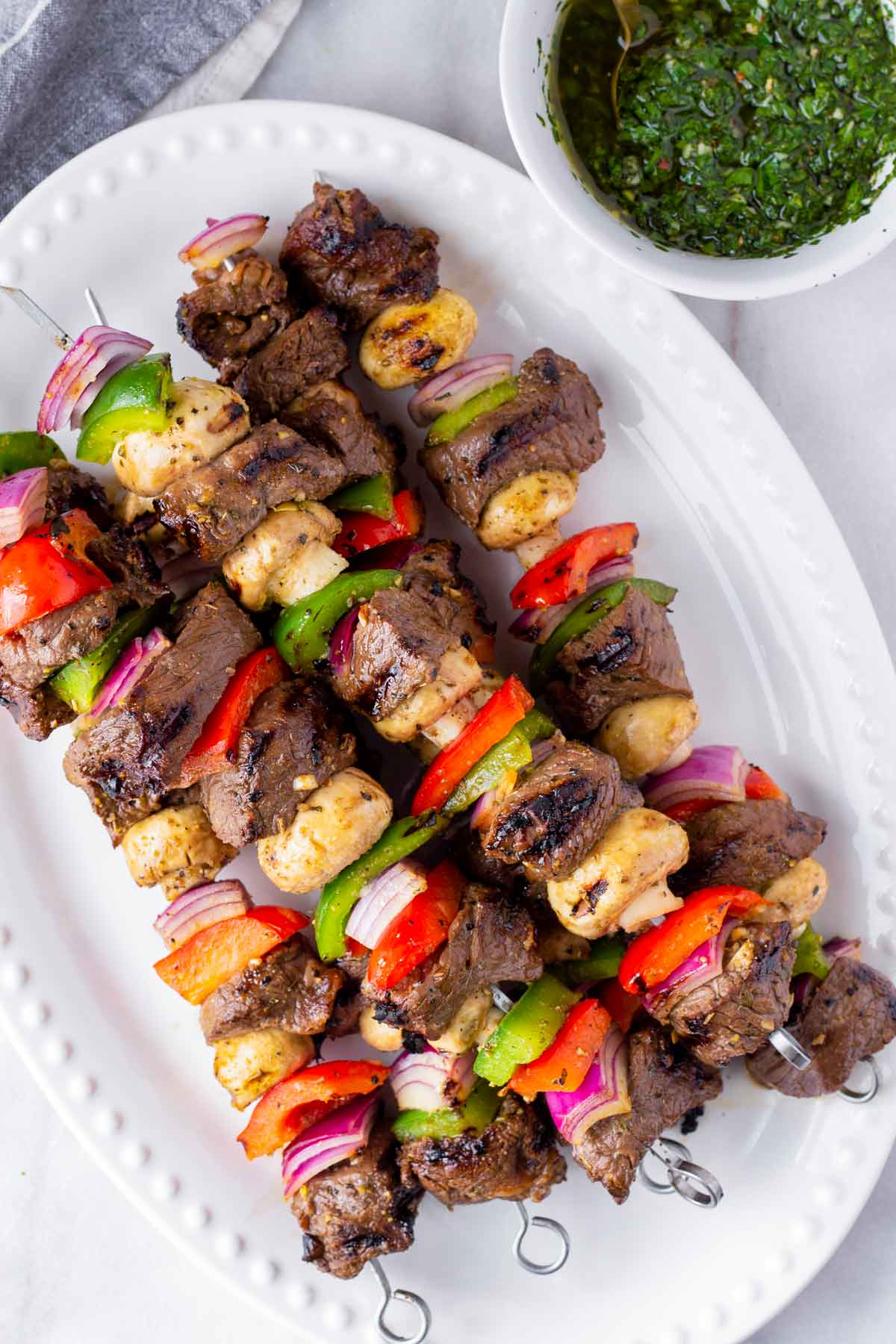 five beef kabobs stacked on top of each other, plus herb sauce