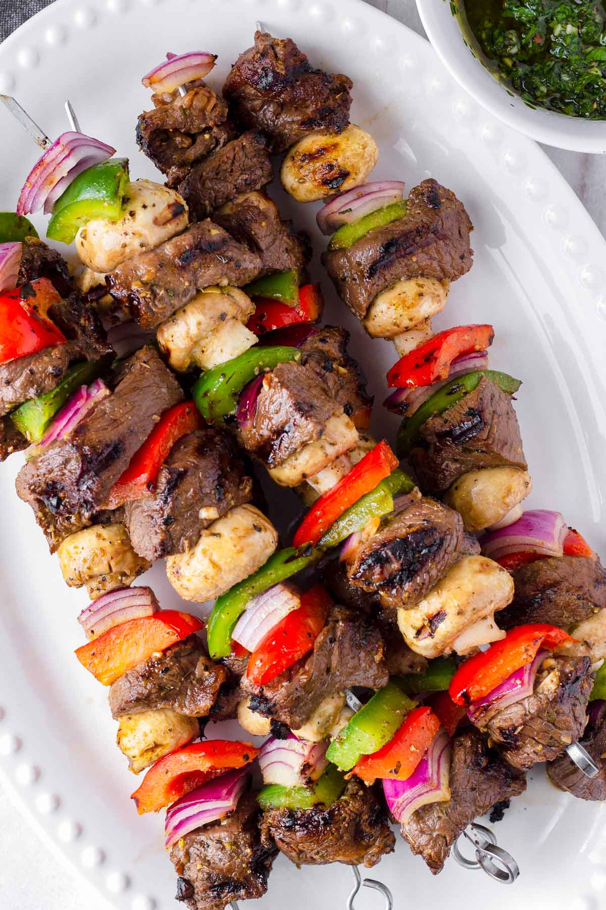 top view of five grilled marinated steak and vegetable kabobs