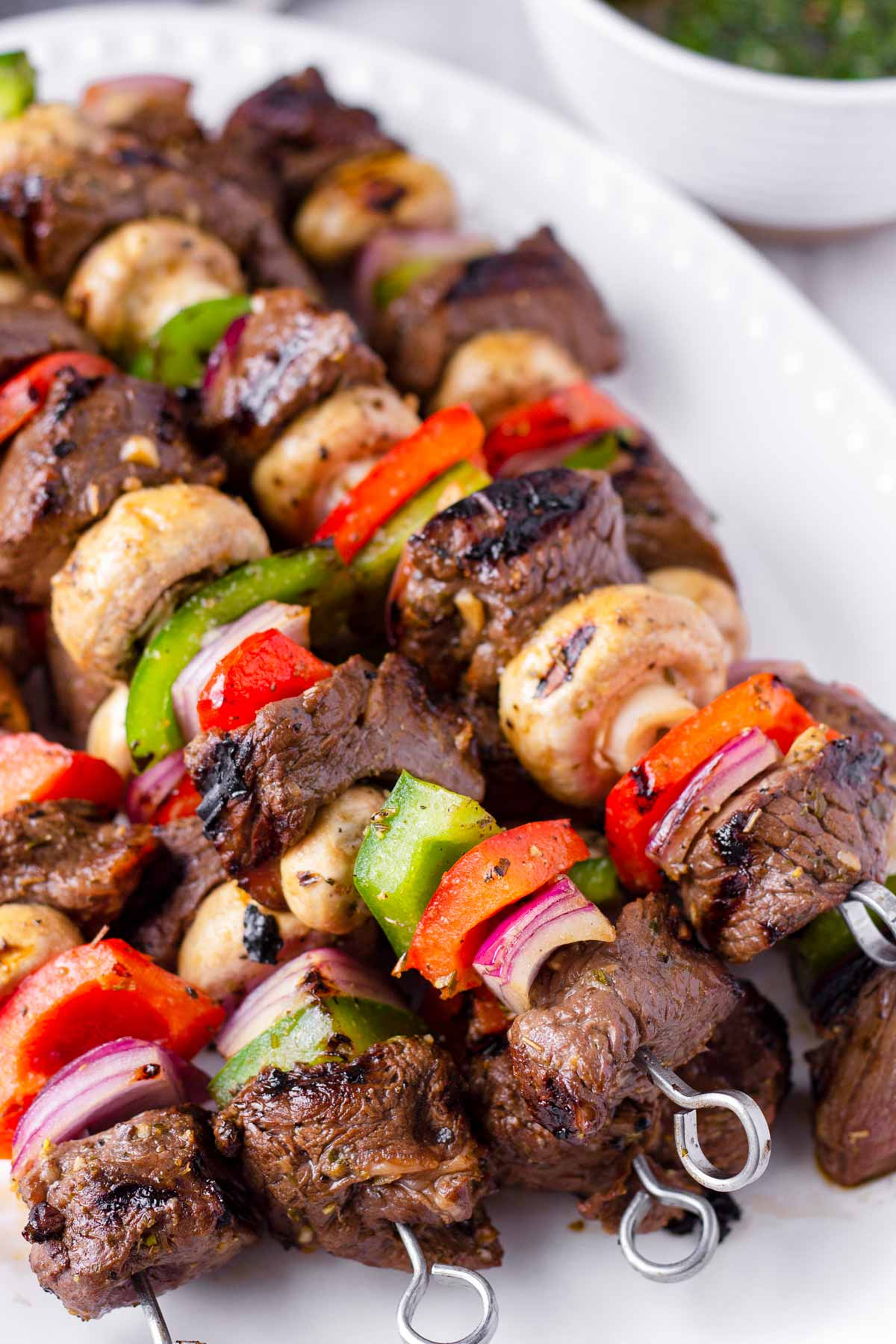 grilled steak kabobs with peppers, mushrooms, and onions on a plate