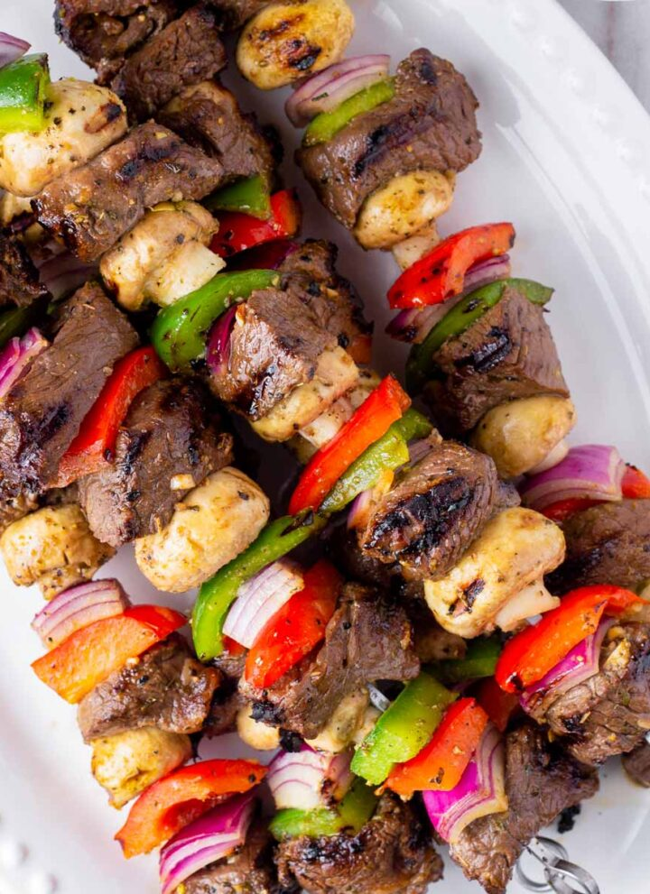 platter with grilled marinated beef kabobs and vegetables