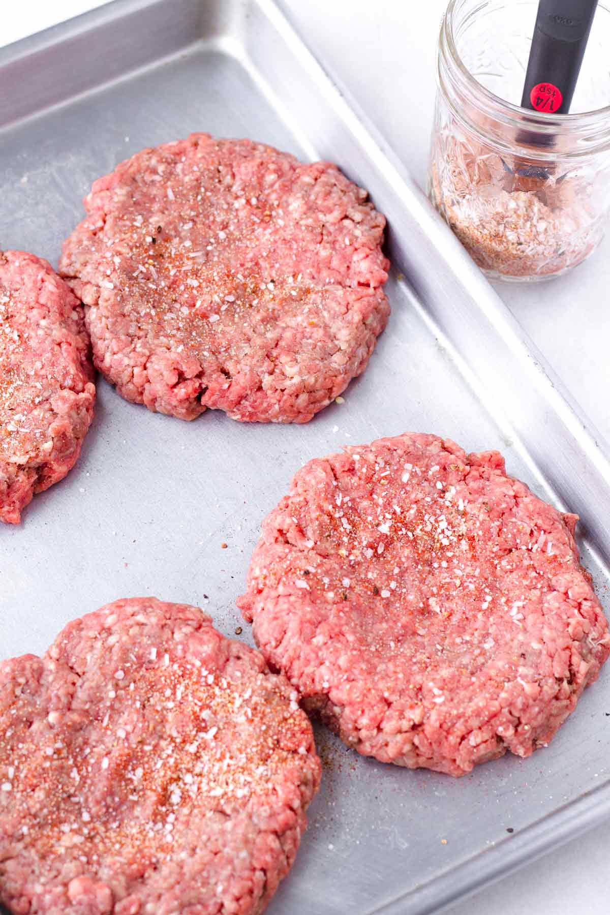 four seasoned meat patties on a sheet pan, next to a mason jar with seasoning