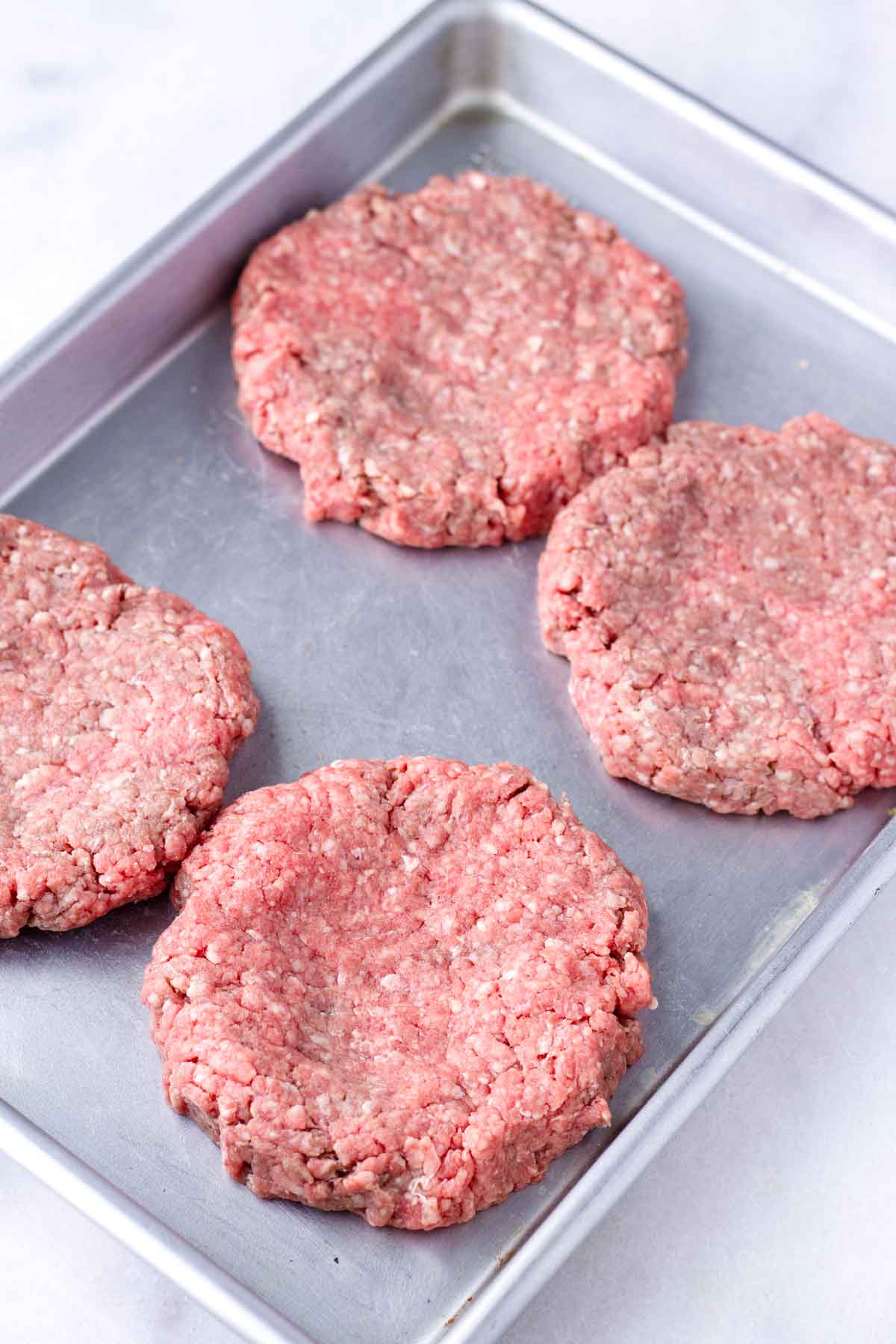 shaped patties with a dent in the middle, arranged on a sheet pan