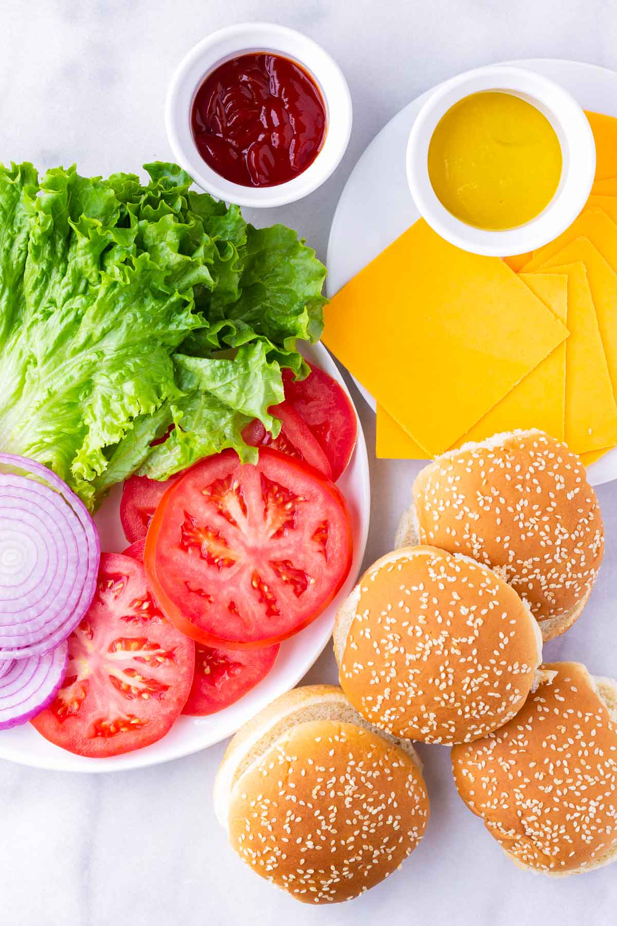 a spread of sesame buns, lettuce, tomatoes, onions, cheddar slices, ketchup, and mustard