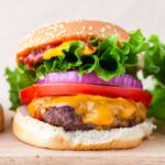 beef burger with lettuce, tomato onion on a sesame bun
