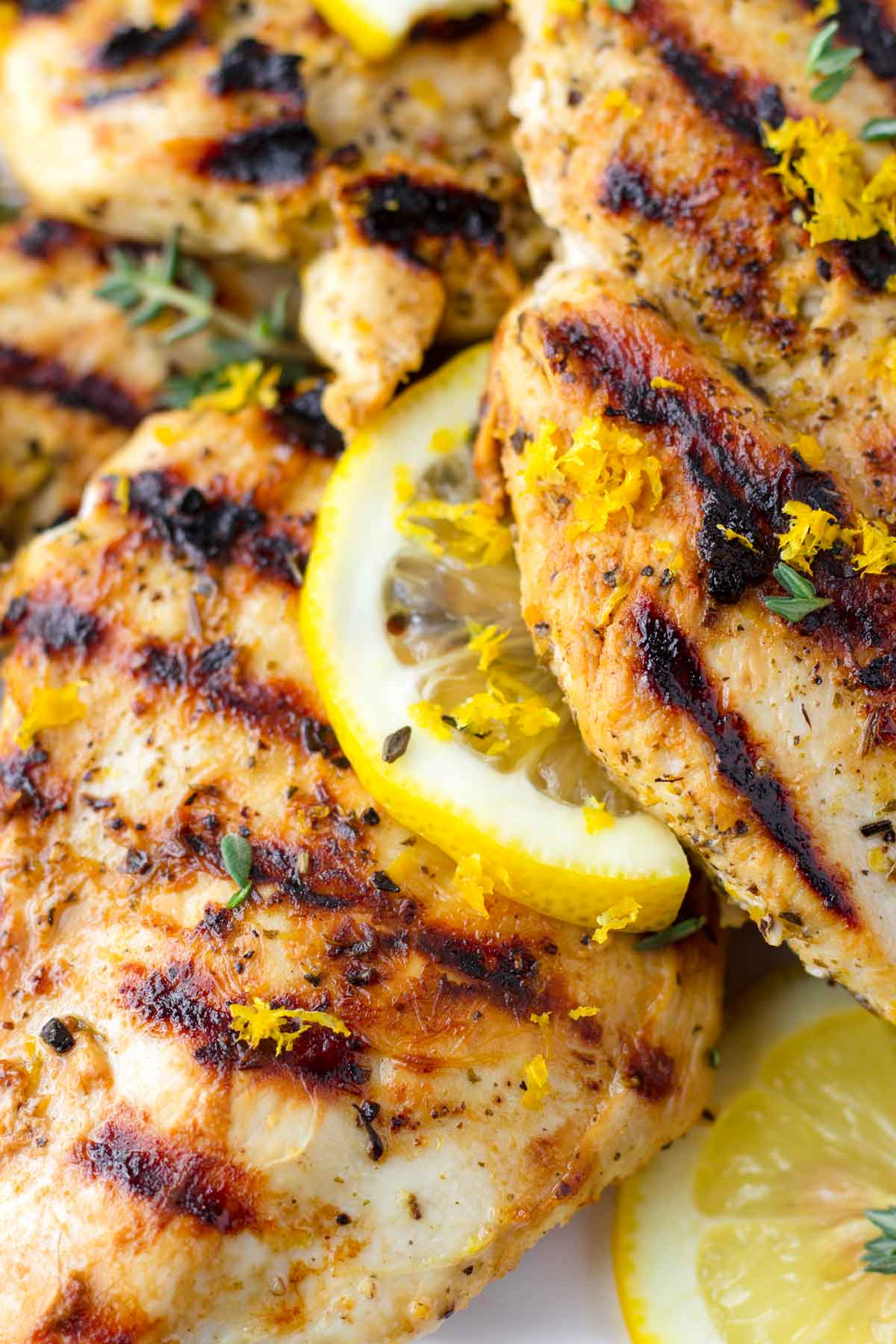 close up of grilled lemon chicken breasts with a slice of lemon and zest