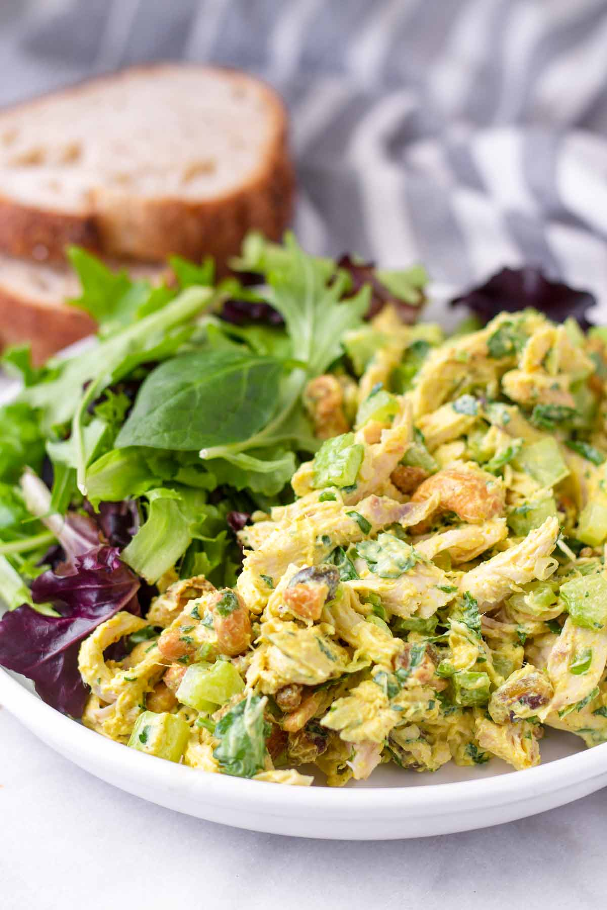 yellow golden chicken curry salad with mixed greens and bread slices
