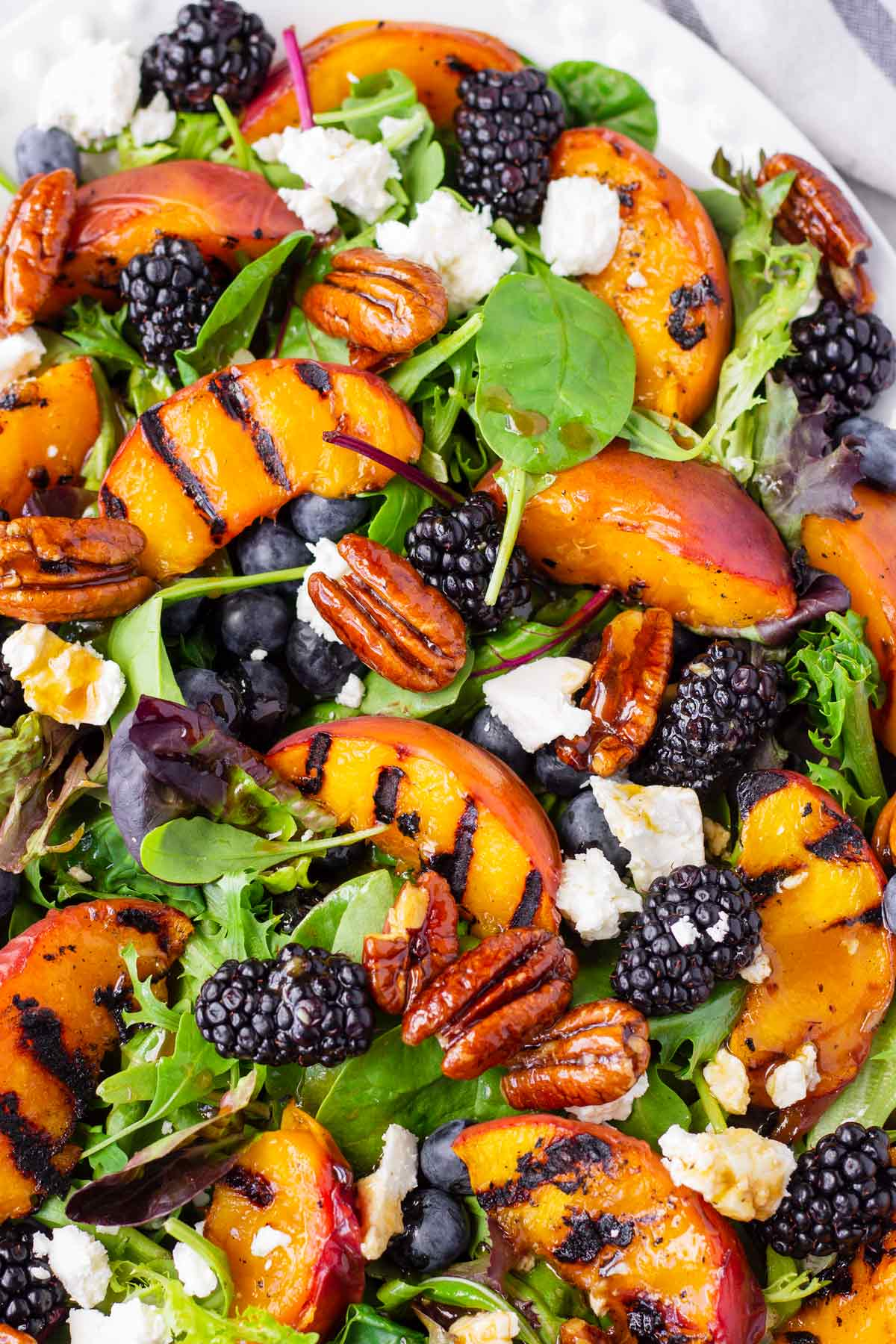 grilled summer peaches on mixed greens, berries, feta, and candied pecans