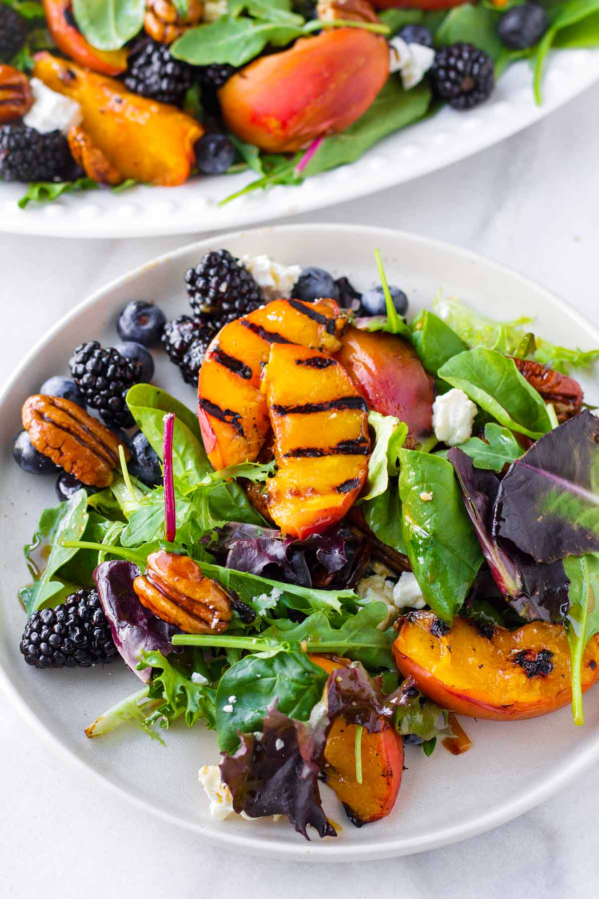 grilled peach salad with berries, mixed greens, pecans, and feta