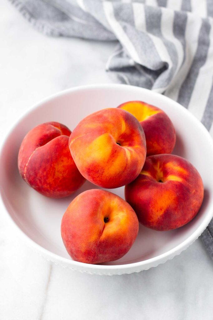 Five peaches on a white bowl with a napkin behind