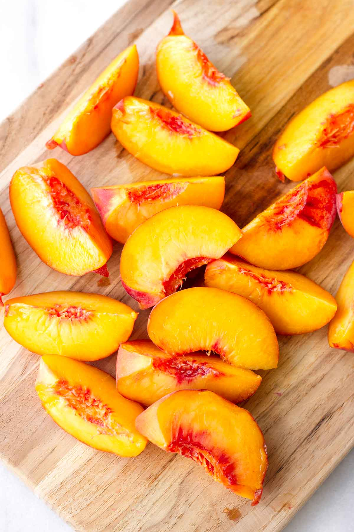 several fresh peach slices on a cutting board