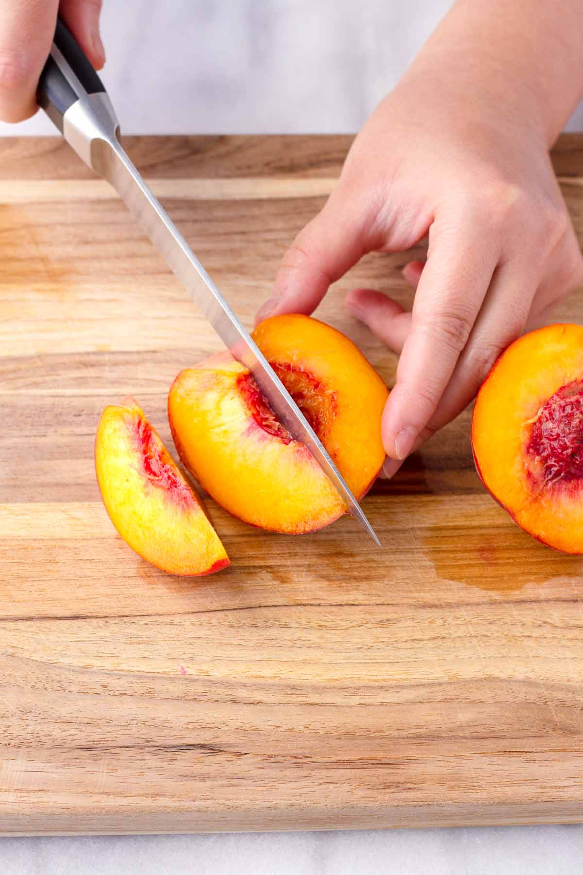 a hand slicing stone fruit into wedges