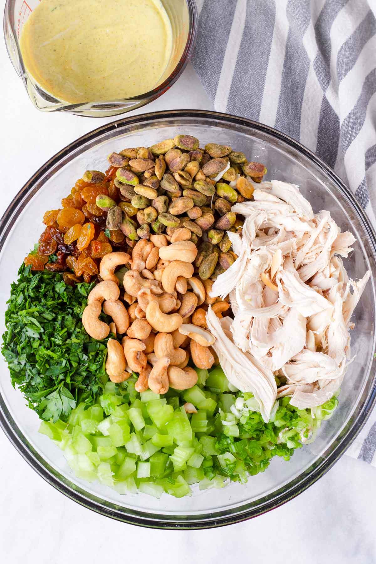 parsley, golden raisins, pistachios, cashews, celery, scallions, shredded chicken in bowl