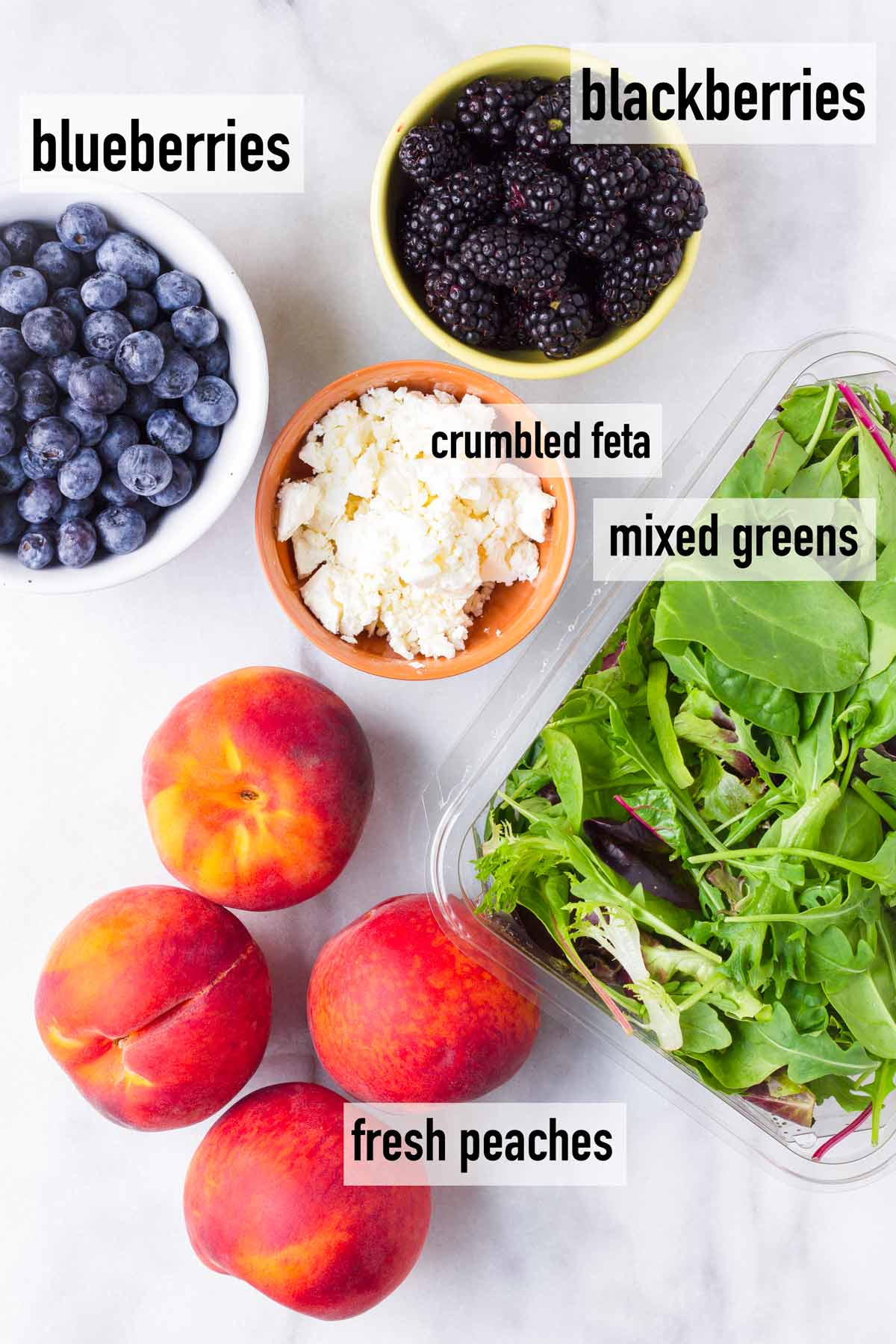 ingredients including berries, peaches, feta, and mixed greens