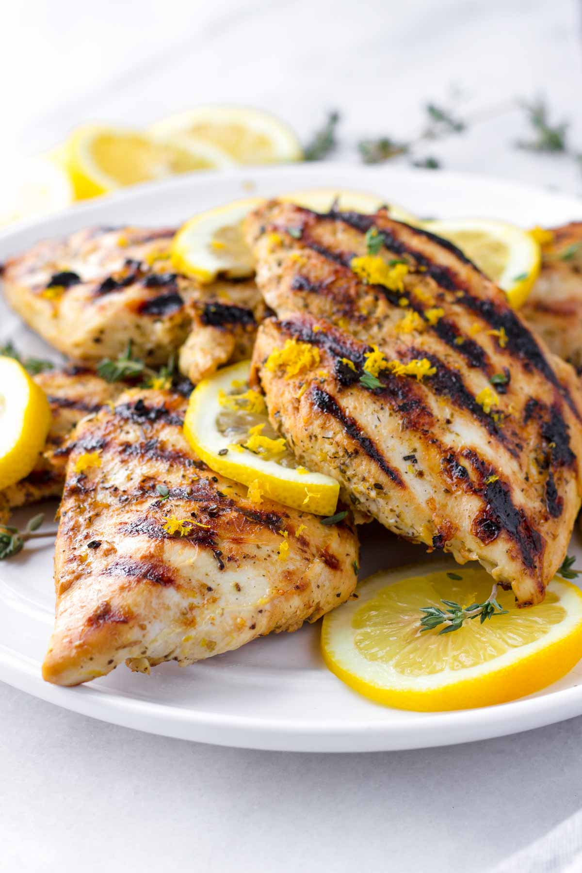 several cooked chicken breasts on a plate with herb and citrus garnish