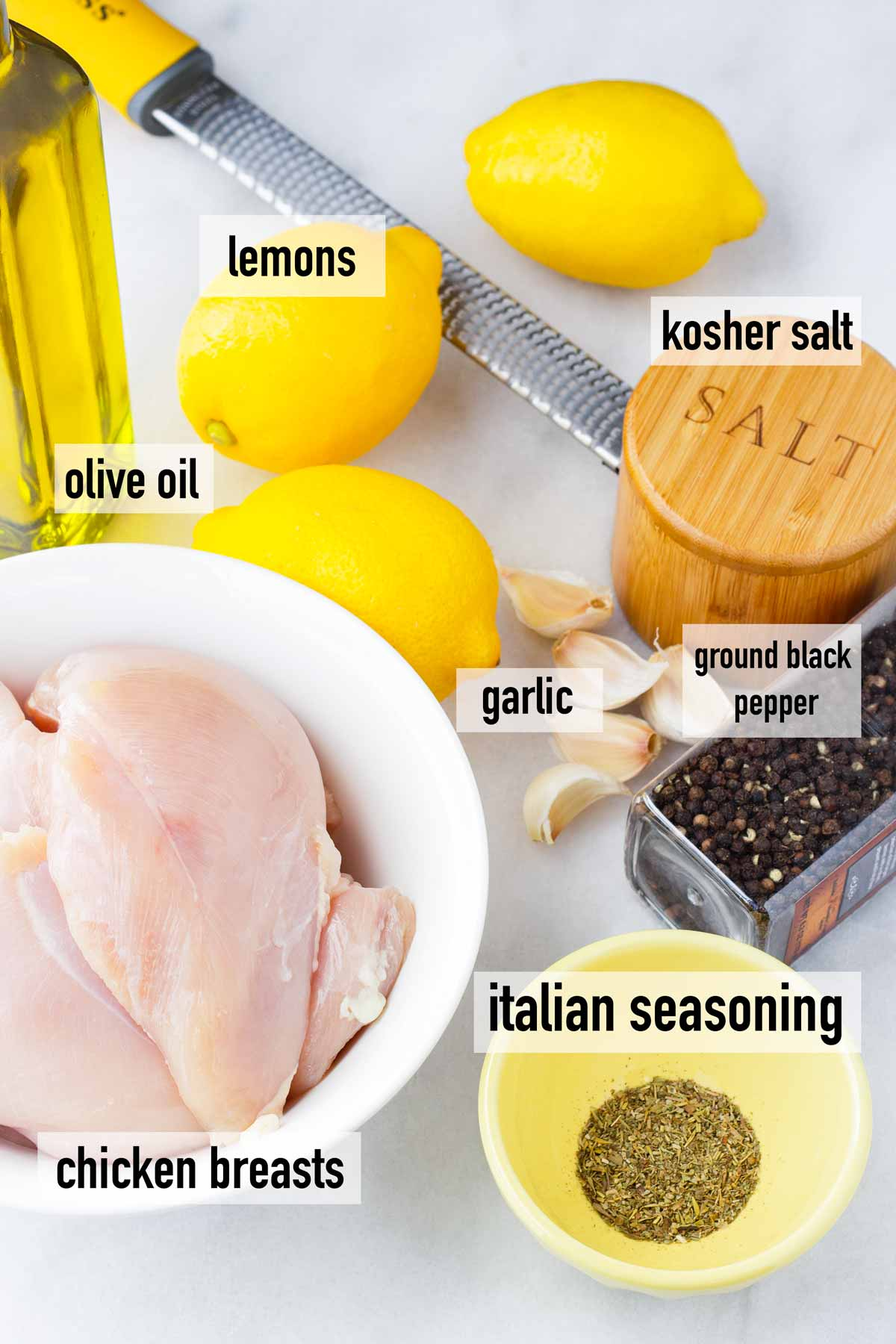 labeled ingredients with olive oil, raw chicken breasts, ground black pepper, dried herbs, salt, and three lemons