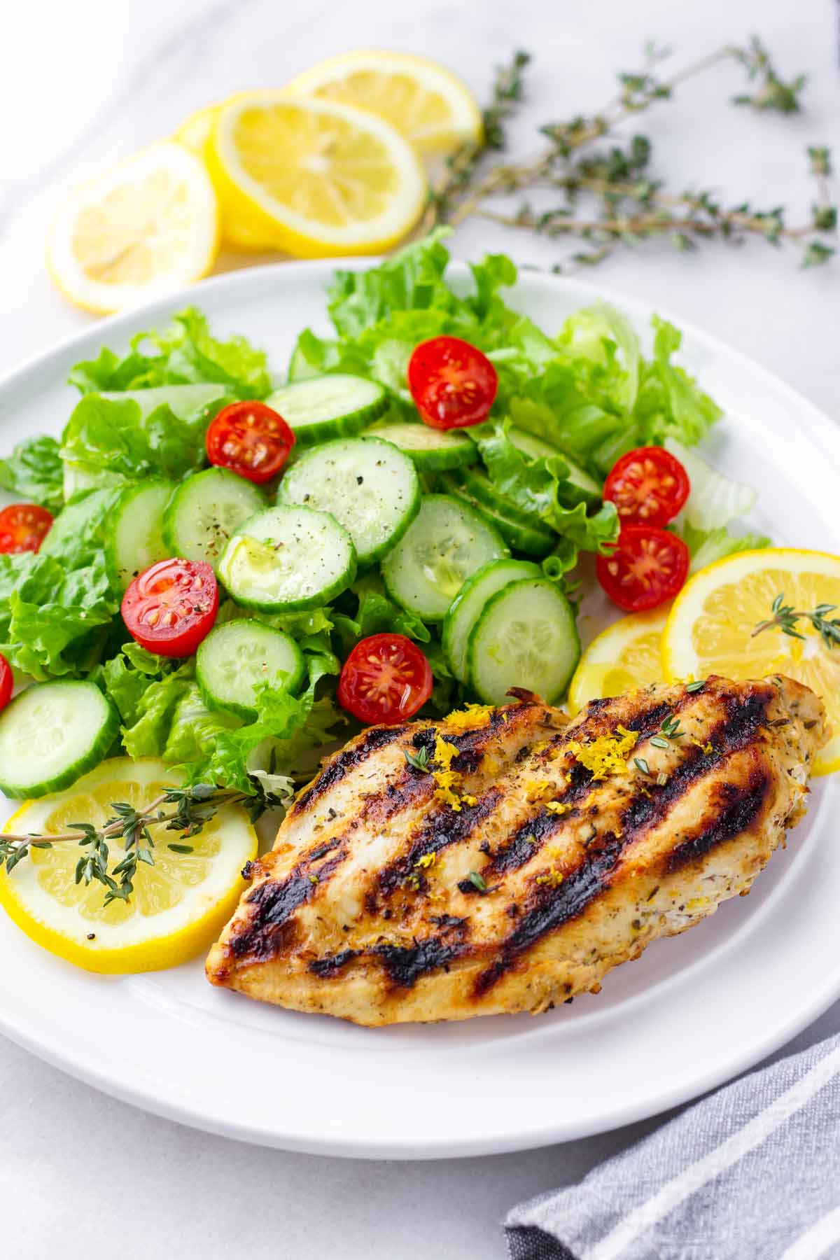 a round plate with lemon marinated grilled chicken served with a side garden salad