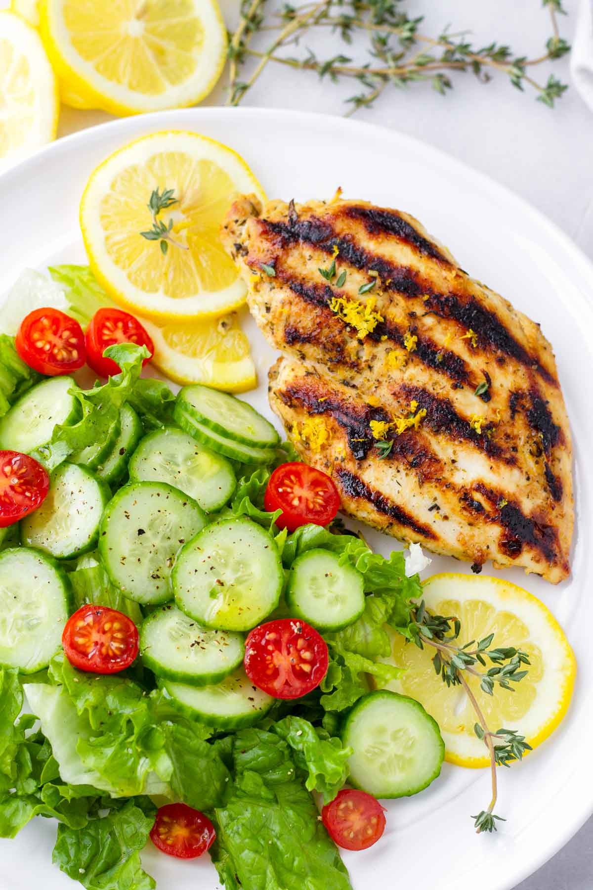 an individual plate with lemon grilled chicken, a green salad, tomatoes, lemons, and thyme