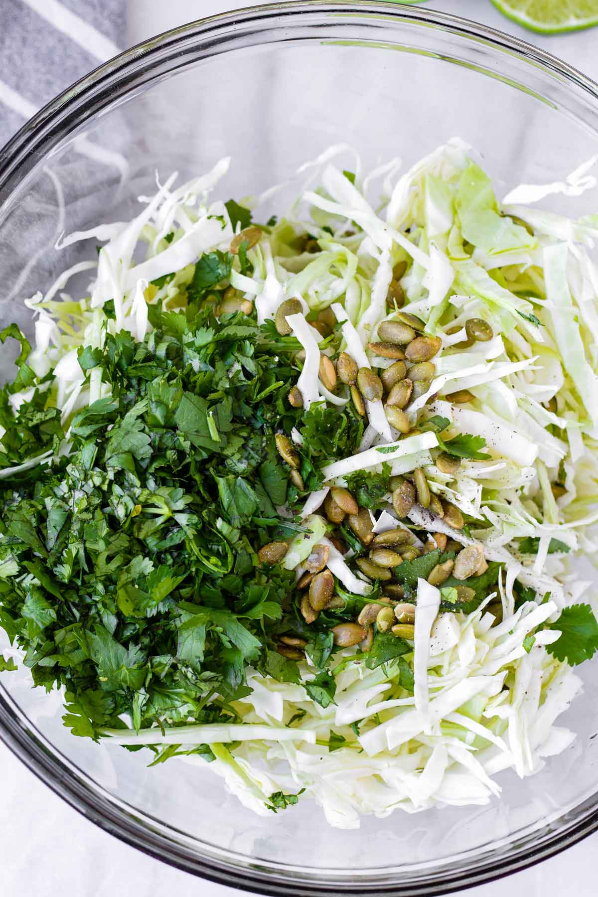 a glass bowl with cilantro, green cabbage, pumpkin seeds