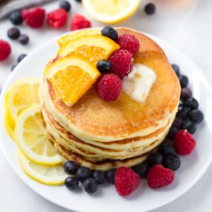 a stack of pancakes with fruit and syrup on top