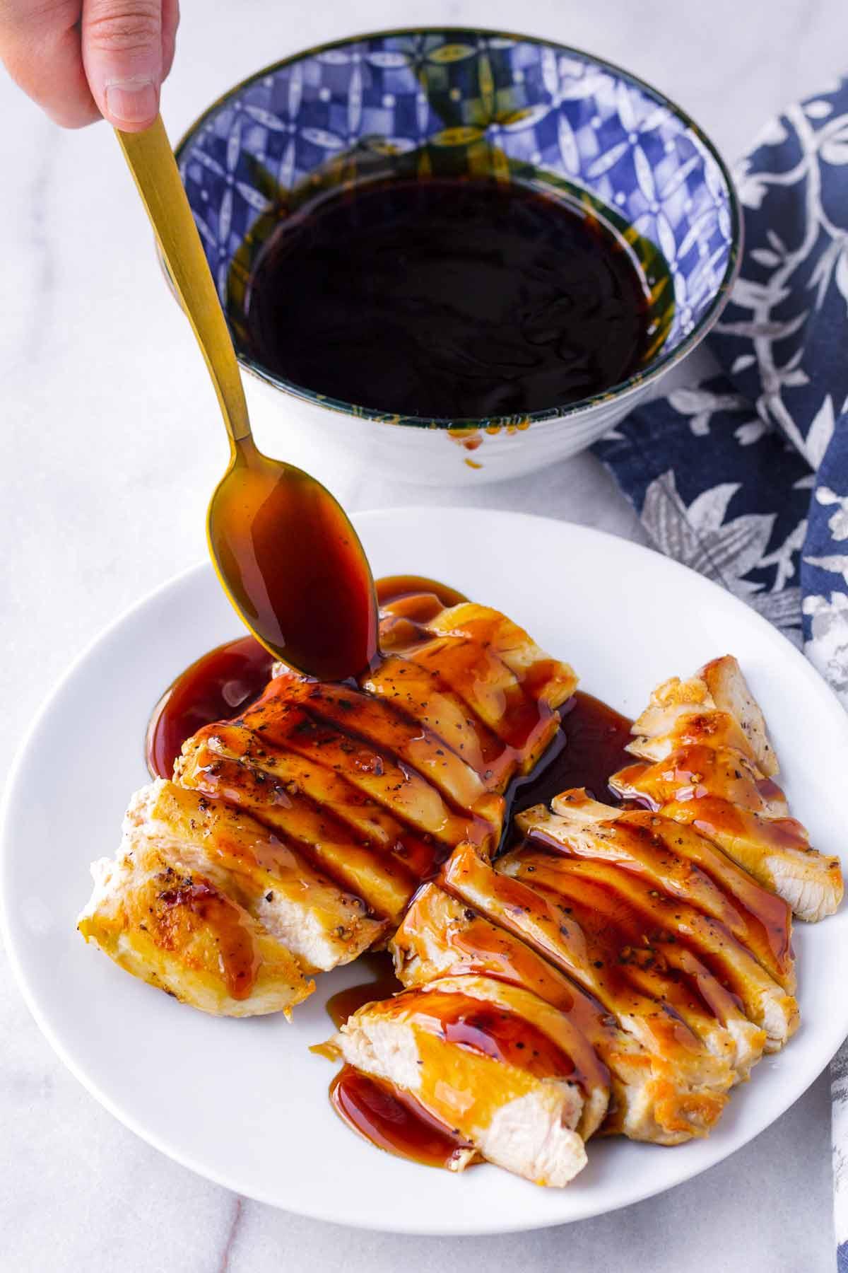 teriyaki sauce being spooned over sliced chicken on plate