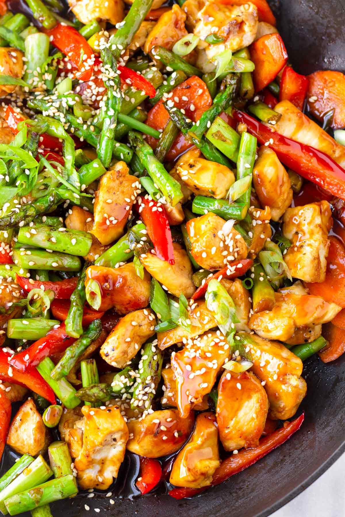 close up of chicken, asparagus, red bell pepper stir fry with sesame seeds